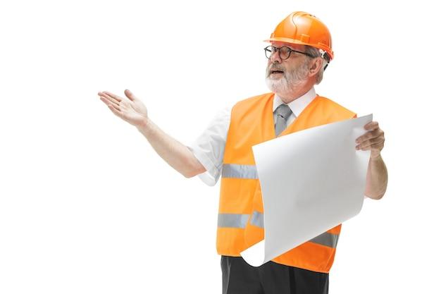 Budowniczy W Kamizelce Budowlanej I Pomarańczowym Hełmie Stojącym Na Białym Tle. Darmowe Zdjęcia
