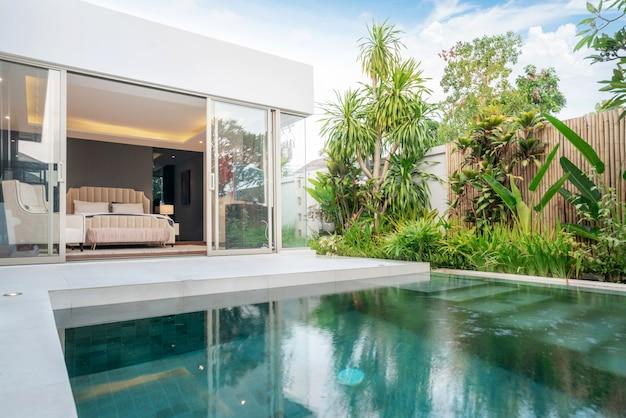 Budynek domu lub domu na zewnątrz i wnętrza przedstawiający tropikalną willę z basenem z zielonym ogrodem Premium Zdjęcia