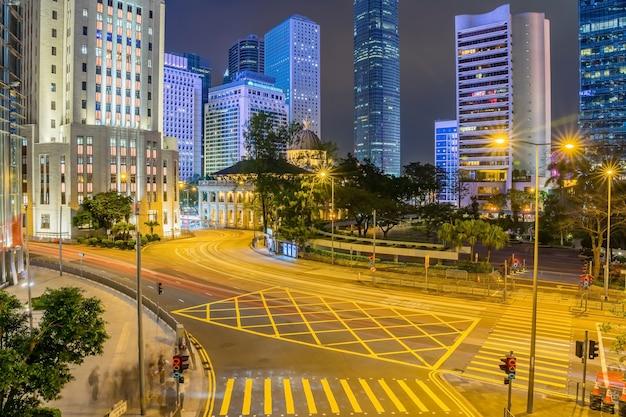 Budynki Wieżowca Biurowego I Ruchliwy Ruch Na Drodze Autostrady Z Niewyraźne Lekkie ślady Samochodów. Premium Zdjęcia