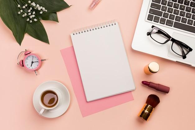 Budzik, filiżanka kawy, notatnik spirala, okulary i laptop z pędzlem do makijażu i szminki na kolorowym tle Darmowe Zdjęcia