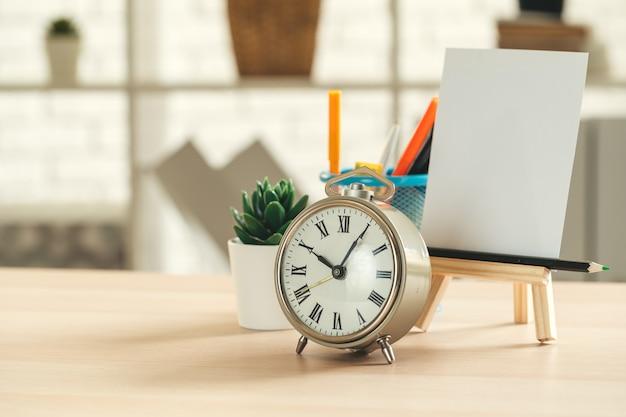 Budzik i biurowe artykuły biurowe z bliska na drewnianym stole Premium Zdjęcia