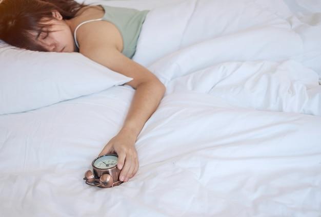 Budzik I Ręka Azjatyckiej Kobiety Zatrzymują Czas W łóżku Podczas Snu, Młoda Dorosła Kobieta Budzi Się Późnym Rankiem. świeży Relaks, Senność I Koncepcje Miłego Dnia Premium Zdjęcia