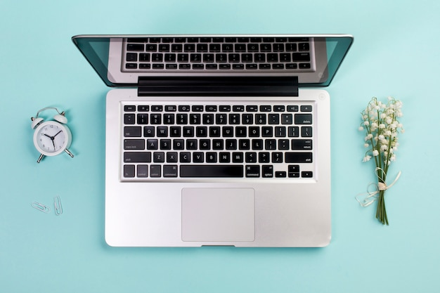 Budzik, spinacz do papieru, bukiet konwalia z otwartym laptopem na niebieskim biurku biznesu Darmowe Zdjęcia