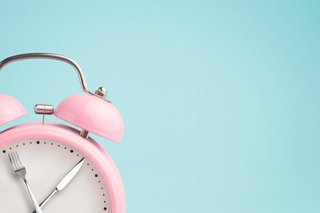 Budzik. widelec i nóż zamiast wskazówek zegara. pojęcie przerywanego postu, przerwy obiadowej, diety i odchudzania Premium Zdjęcia