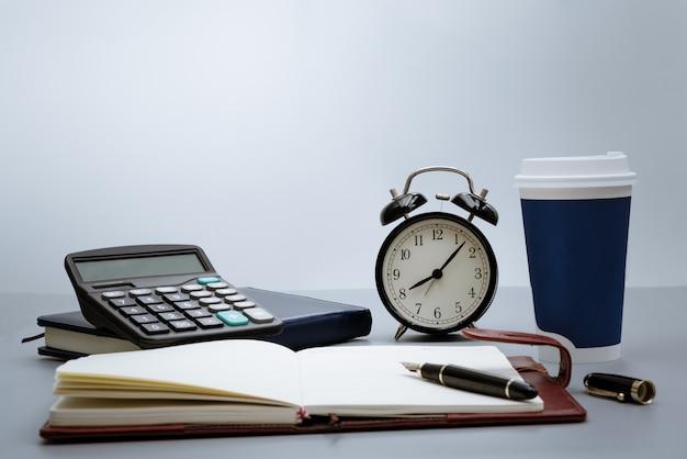 Budzik z notatnikiem, kalkulatorem, piórem i filiżanką kawy na szarym tle Premium Zdjęcia