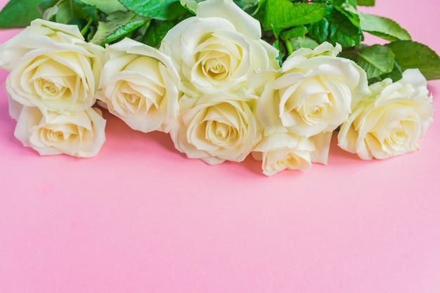 Bukiet Białych Kwitnących Róż Na Pastelowym Różowym Tle. Romantyczna Ramka W Kwiaty. Skopiuj Miejsce Premium Zdjęcia