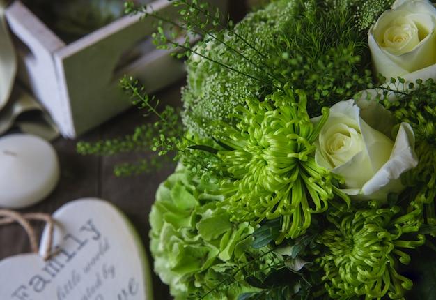 Bukiet białych róż i zielonych chryzantem z drewnianymi symbolami dookoła. Darmowe Zdjęcia