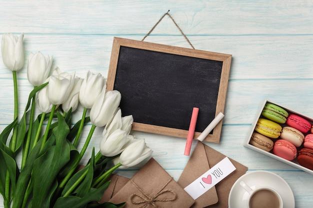 Bukiet Białych Tulipanów Z Kredową Deską, Filiżanką Kawy, Miłości Notatką I Macarons Na Błękitnych Drewnianych Deskach Premium Zdjęcia