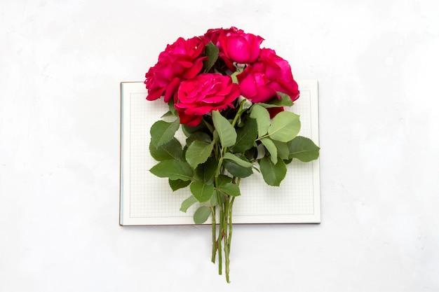 Bukiet Czerwonych Róż Na Otwartym Pamiętniku Na Jasnym Tle Kamienia. Leżał Płasko, Widok Z Góry Premium Zdjęcia