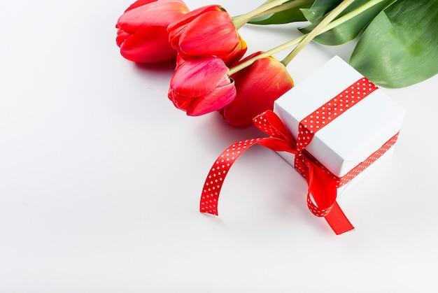 Bukiet Czerwonych Tulipanów, żonkile I Prezent Na Białym Tle Premium Zdjęcia