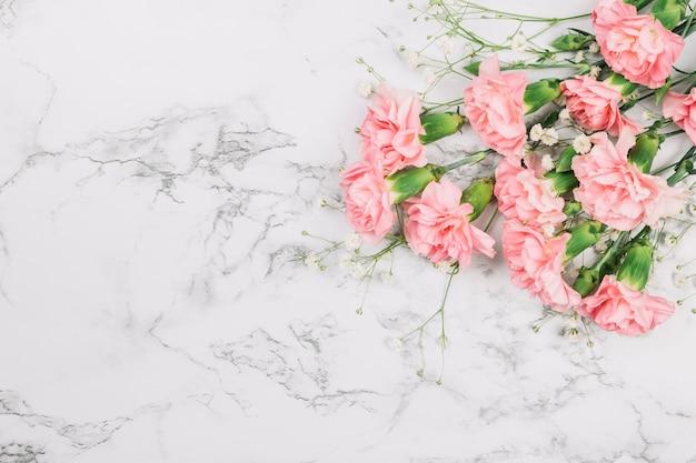 Bukiet kwiatów i bukiet goździków dziecka na rogu marmurowego tła Darmowe Zdjęcia
