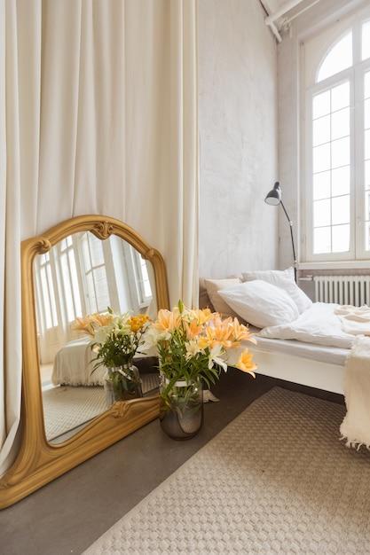 Bukiet Kwiatów I Lustro Umieszczone Obok Zasłony I Wygodnego łóżka W Eleganckiej Sypialni W Domu Premium Zdjęcia
