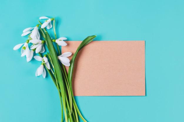 Bukiet Kwiatów Przebiśniegów I Papieru Rzemieślniczego Do Notatek Na Niebieskim Tle Mieszkanie Leżał Widok Z Góry Premium Zdjęcia