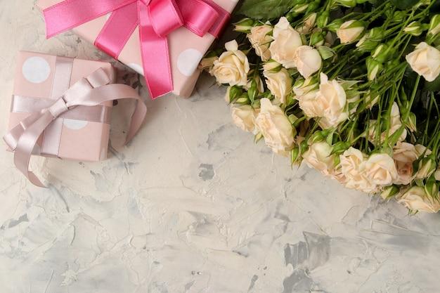 Bukiet Pięknych Delikatnych Mini Róż I Pudełko Na Jasnym Tle Betonu Premium Zdjęcia