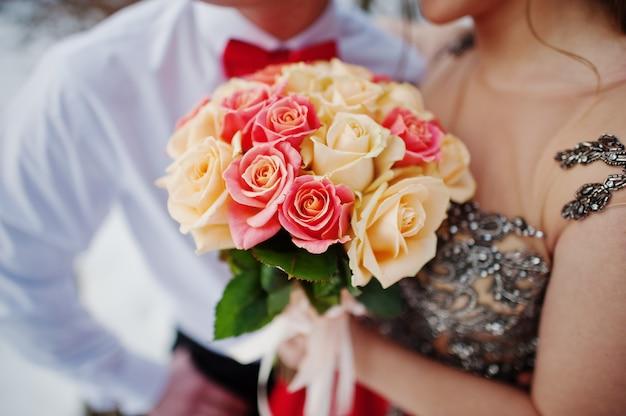 Bukiet róż w rękach pary. Premium Zdjęcia
