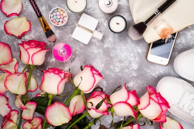 Bukiet Róż Z Kosmetyków W Perfumy, Telefon I Trampki Na Szarym Tle Premium Zdjęcia