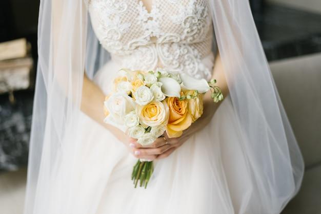 Bukiet ślubny biały i pomarańczowy w rękach panny młodej Premium Zdjęcia