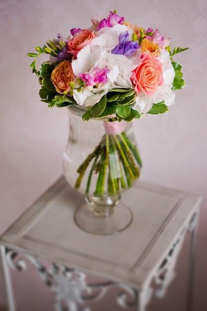 Bukiet ślubny Z Kwiatów, Piwonii, Róż, Stoi W Garnku Z Wodą Na Stole Premium Zdjęcia