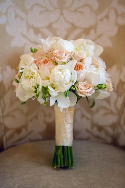 Bukiet ślubny Z Piwonii Leżących Na Krześle Premium Zdjęcia