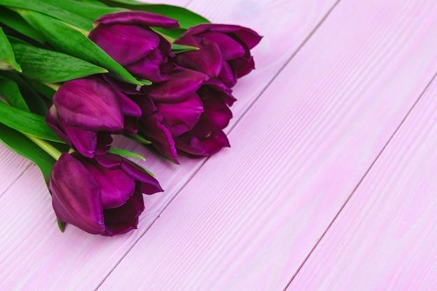 Bukiet tulipan kwitnie na różowym drewnianym tle z copyspace Premium Zdjęcia
