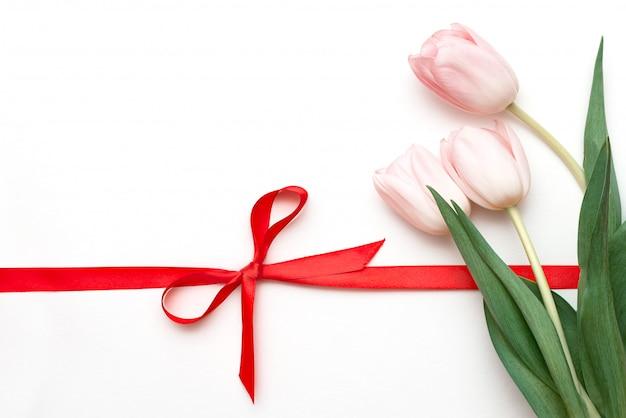 Bukiet Tulipanów Na Białym Tle Z Czerwoną Wstążką Związany W łuk Premium Zdjęcia