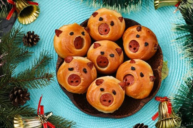 Bułeczki świnie Nadziewane Kiełbasą Na Niebieskim Tle, Widok Z Góry, Pomysł Na Nowy Rok I Wakacje Dla Dzieci Premium Zdjęcia