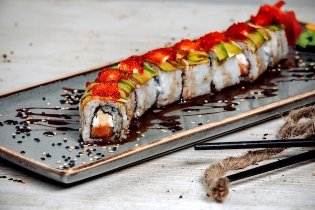 Bułki sushi pokryte awokado, śmietaną i czerwonym tobiko oraz sosem sojowym Darmowe Zdjęcia