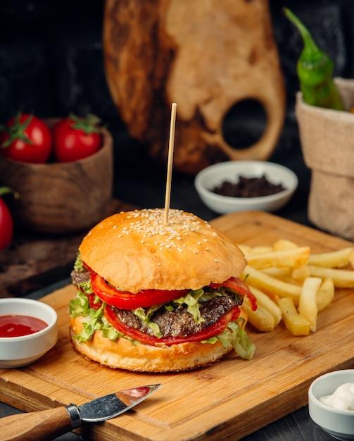 Burger w bułce z ziemniakami na desce. Darmowe Zdjęcia
