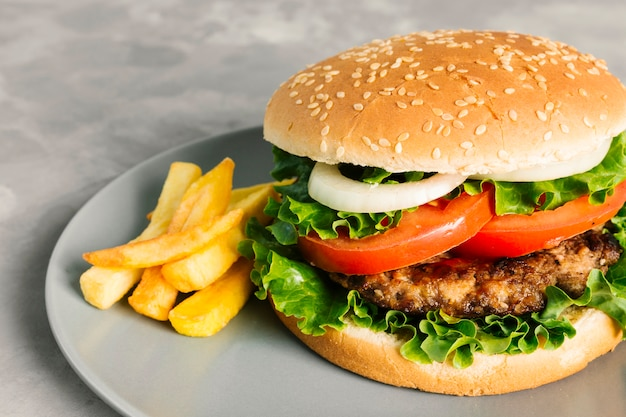 Burger z bliska z dużym frytkami na talerzu Darmowe Zdjęcia