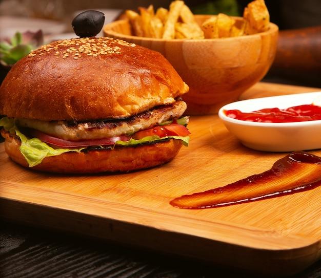 Burger Z Mięsem Z Kurczaka Z Pomidorami I Sałatą Wewnątrz I Frytkami Podawanymi Z Czarną Oliwą I Keczupem Na Drewnianej Tacy Darmowe Zdjęcia