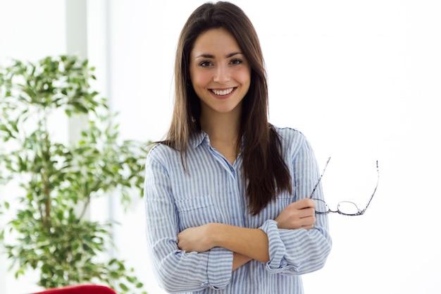 Business młoda kobieta spojrzenie na aparat fotograficzny w biurze. Darmowe Zdjęcia