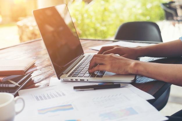 Business woman strony wpisując na klawiaturze laptopa z cha finansowego Darmowe Zdjęcia