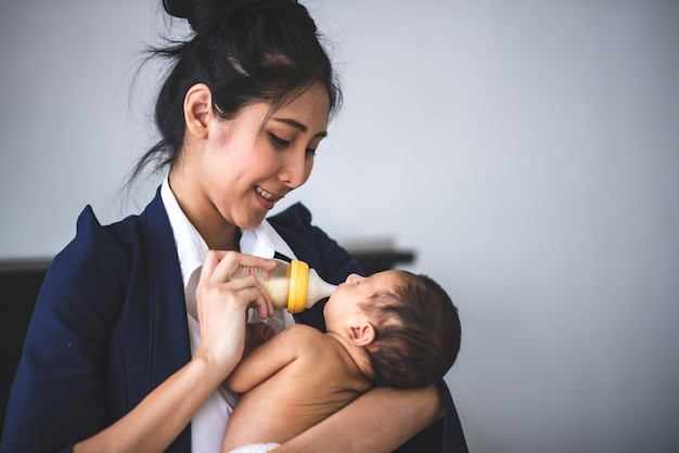 Businesswoman pracy z domu, trzymając córeczkę Premium Zdjęcia