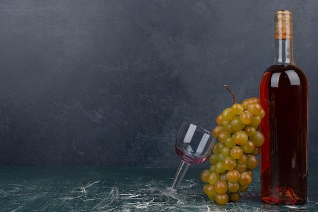 Butelka Czerwonego Wina I Winogrona Na Marmurowym Stole Darmowe Zdjęcia