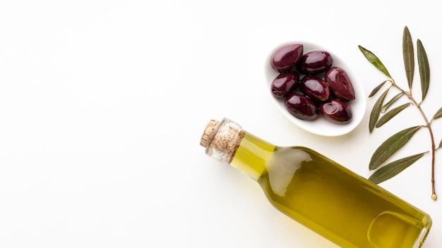 Butelka oliwy z oliwek z liśćmi i fioletowymi oliwkami z miejsca kopiowania Darmowe Zdjęcia