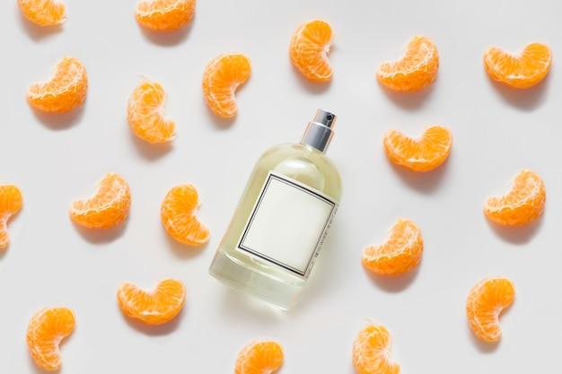 Butelka Pachnącego Oleju Lub Perfum Na Białej ścianie Ozdobiona Plasterkami Mandarynki. Koncepcja Cytrusowych Perfum Lub Aromaterapii, Owocowe Aromaty. Premium Zdjęcia