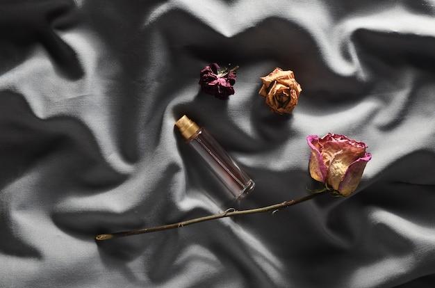 Butelka Perfum I Pąków Suszonych Róż Na Szarym Jedwabiu. Romantyczny Wygląd. Widok Z Góry. Premium Zdjęcia