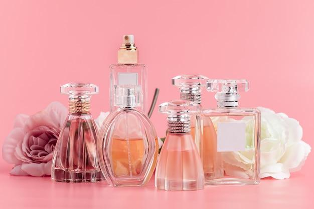 Butelka Perfum Z Różami Na Różowym Materiale Premium Zdjęcia
