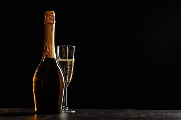 Butelka szampana i szkła na ciemnym tle Premium Zdjęcia