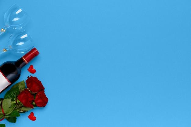 Butelka Wina Z Róż I Kieliszki Do Wina Na Niebieskim Tle Premium Zdjęcia