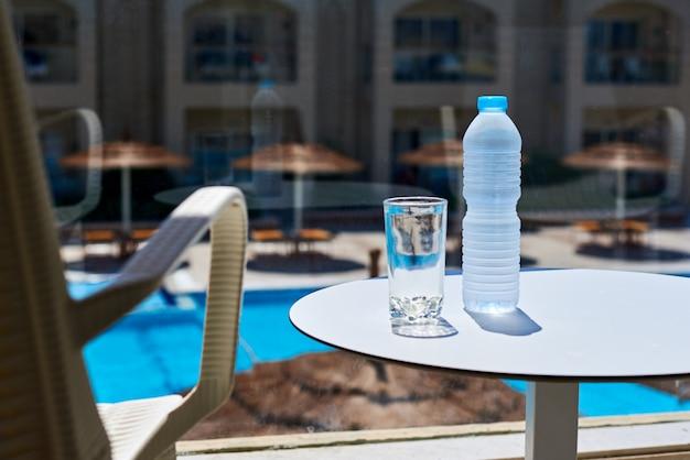Butelka wody i szklanki na stole na tarasie w hotelu przed basenem z wodą Premium Zdjęcia