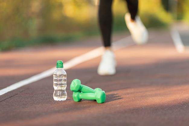 Butelka Wody I Zielonych Odważników Premium Zdjęcia