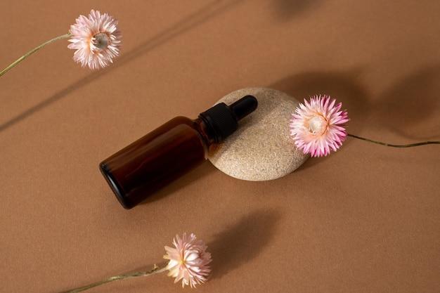 Butelka Z Brązowego Szkła Z Olejkiem Kosmetycznym Z Różowymi Suchymi Kwiatami Na Tle Terakoty Widok Z Przodu, Zbliżenie Premium Zdjęcia