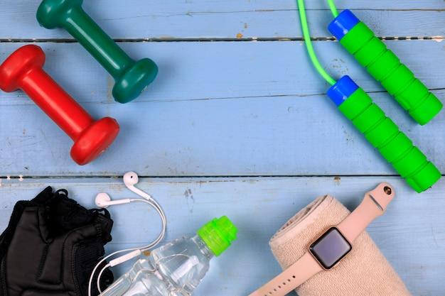 Butelka z wodą, elegancki zegarek, słuchawki i skakanka. copyspace Premium Zdjęcia