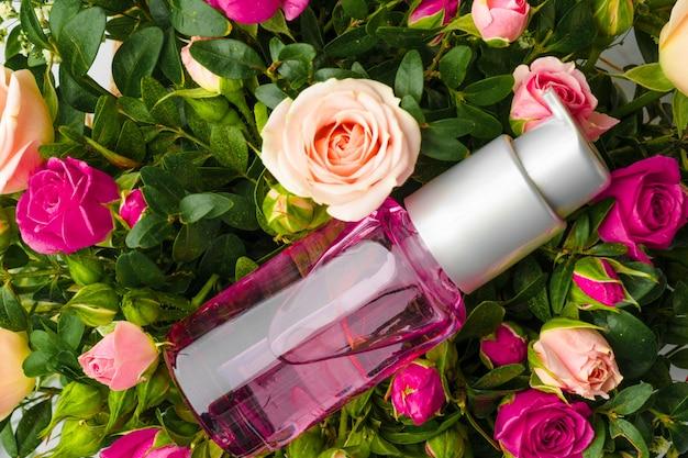Butelka Zapachu Lub Olejku Aromatycznego W Wiązce świeżych Kwiatów Premium Zdjęcia