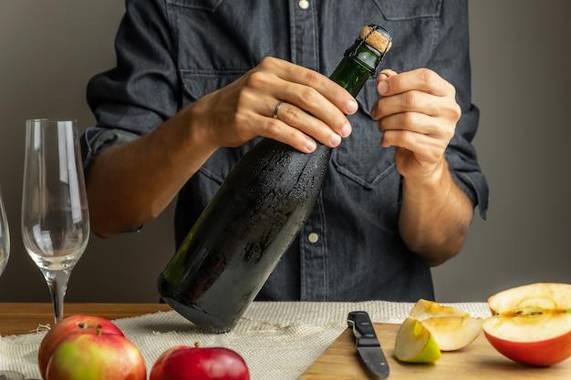 Butelki Otwierające Do Rąk Męskiej Klasy Premium. Odkorkowanie Pięknej Lodowatej Butelki Wina Jabłkowego Premium Zdjęcia