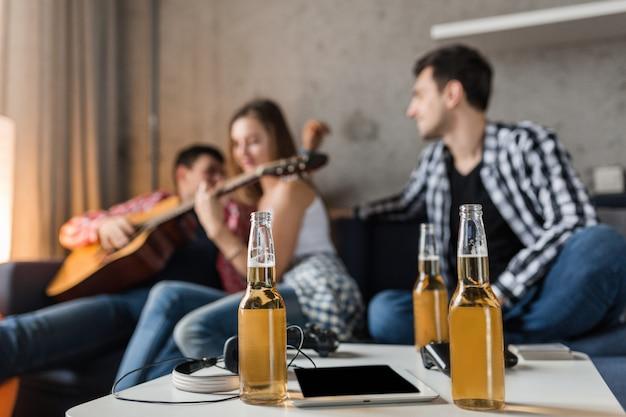 Butelki Piwa Na Stole I Szczęśliwi Młodzi Ludzie Bawią Się Na Tle, Przyjęcie Z Przyjaciółmi W Domu, Firma Hipster Razem, Dwóch Mężczyzn, Jedna Kobieta, Gra Na Gitarze, Spędzać Czas Darmowe Zdjęcia