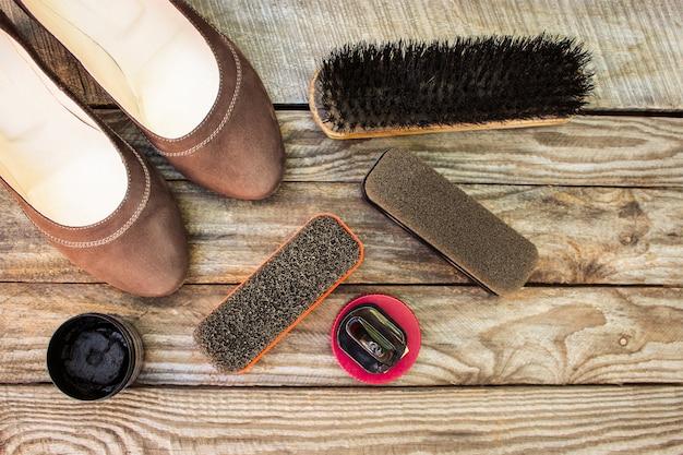Buty damskie i produkty do pielęgnacji obuwia na drewnianym tle. Premium Zdjęcia