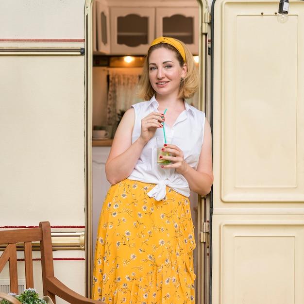 Buźka Kobieta Trzyma Szklankę Lemoniady Obok Przyczepy Kempingowej Darmowe Zdjęcia