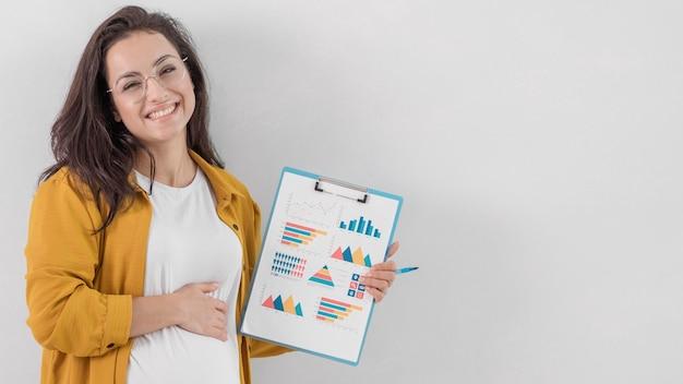 Buźka Kobieta W Ciąży Trzymając Schowek I Jej Brzuch Darmowe Zdjęcia